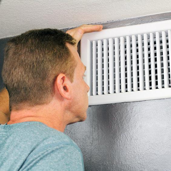 man peeking inside vent