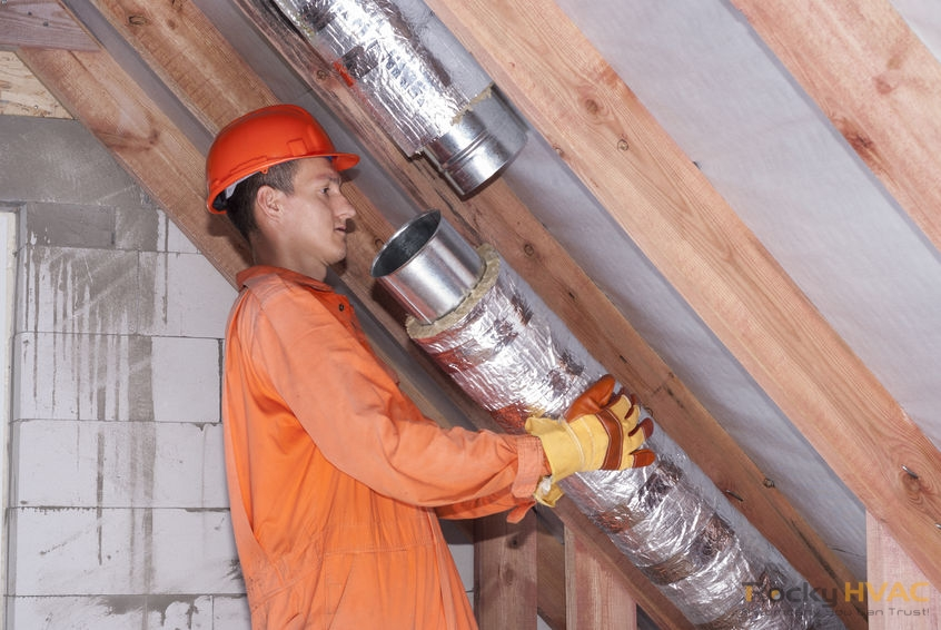 A Picture of a Man Connects Metal Air Ducts.