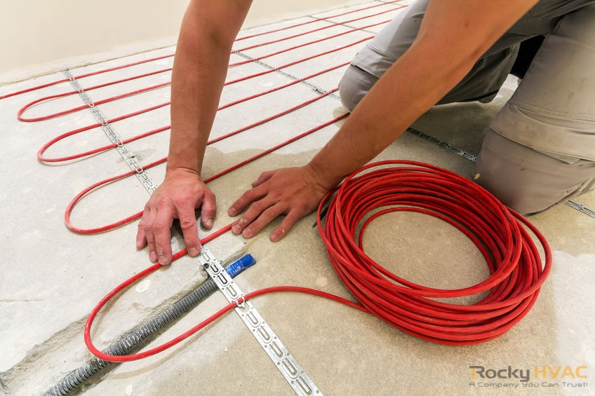 Worker installing heating cable for warm floor.
